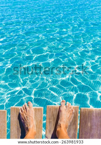 sandy feet on the pier under tropical turquoise water sea ocean - stock photo
