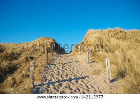 Sandy pathway between dunes leading towards the North Sea on Sylt island, Germany - stock photo