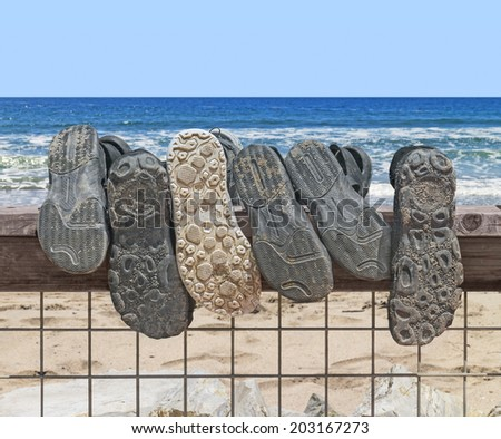Sandy shoe and sandal soles hanging over a wood and metal wire fence on the beach. Walking on the beach concept. Sand in shoe tread. Blue ocean water waves, sky, horizon in background.  - stock photo