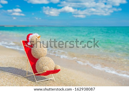 Sandy snowman in red santa hat sunbathing in beach lounge. Holiday concept for New Years and Christmas Cards. - stock photo