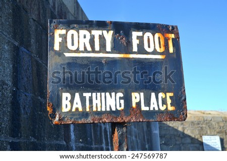 SANDYCOVE, IRELAND - OCTOBER 18: The rusty, hand painted main signpost at the entrance to the famous Forty Foot bathing place on October 18, 2014 in Sandycove, Ireland. - stock photo