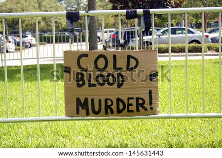 SANFORD, FL - JULY 9, 2013: A cardboard protest sign hangs on the fence outside the Zimmerman murder trial at the Seminole County Criminal Justice Center in Sanford, Florida, on July 9, 2013. - stock photo