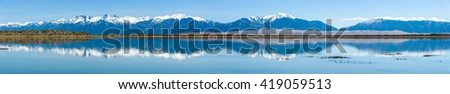 Sangre de Cristo Range and Great Sand Dunes - Panoramic spring view of Sangre de Cristo Range and Great Sand Dunes, looking from San Luis Lake, Colorado, USA. - stock photo