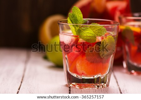 Sangria with citrus fruits, ice cubes and mint leaves in glasses - stock photo