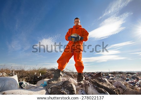 Sanitation worker standing among garbage bags holding a volleyball ball - stock photo