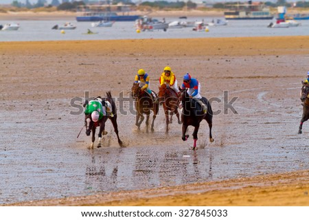 SANLUCAR DE BARRAMEDA, CADIZ, SPAIN - AUGUST 11: Unidentified riders of the accidented horses races of the beach of Sanlucar de Barrameda on August 11, 2011 in Sanlucar de Barrameda, Cadiz, Spain. - stock photo
