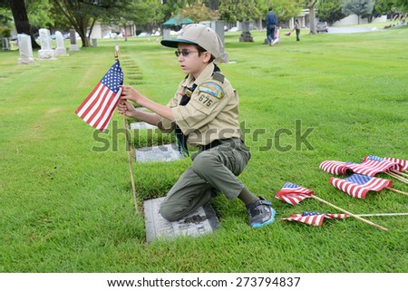 SANTA ANA, CA - MAY 25, 2013: Boy Scout placing flags next to grave sites of veterans at Fairhaven Memorial Park and Mortuary in preparation for Memorial Day services. - stock photo