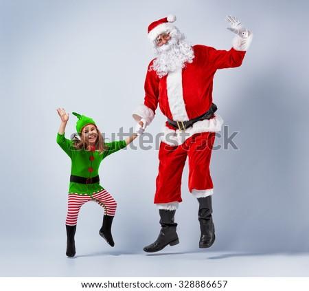 Santa and elf having fun and dancing. - stock photo