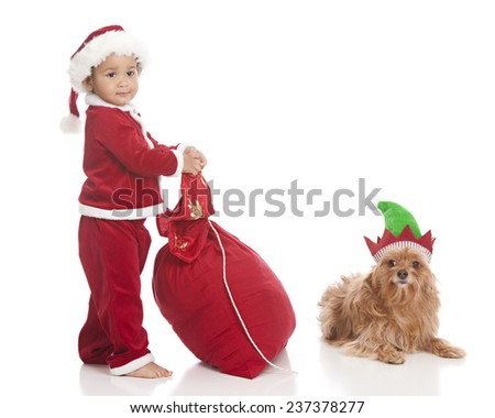 Santa and his little helper.  Adorable biracial toddler dressed as Santa Clause and pulling his sack next to a small dog dressed in an elf hat.  Isolated on white with room for your text. - stock photo