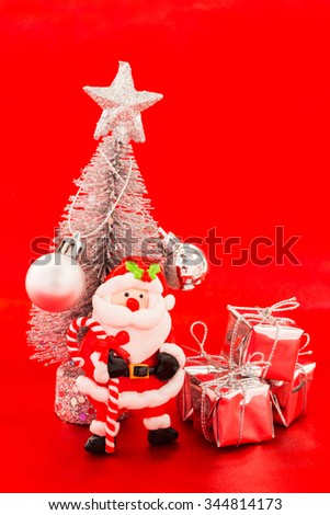 Santa and snow christmas tree with silver present on red background - stock photo