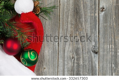 Santa cap, ball ornaments and evergreen branch with pine cones on rustic wood. Christmas concept in horizontal layout.  - stock photo