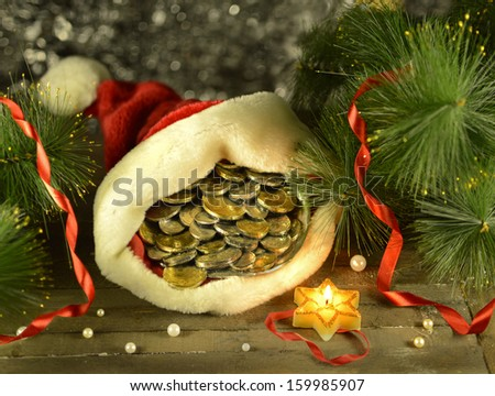 Santa cap with money and burning candle on blurred background - stock photo
