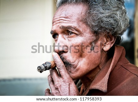 SANTA CLARA,CUBA-JAN 10:Unidentified Cubans smoking cigar on Jan  10. 2010.Santa Clara,Cuba.Cubans of all ages are actively smoking cigars.All production in Cuba is controlled by the Cuban government - stock photo