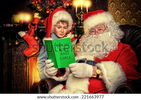 Santa Claus and a cute boy reading a list of good boys and girls. Christmas home d�©cor.  - stock photo