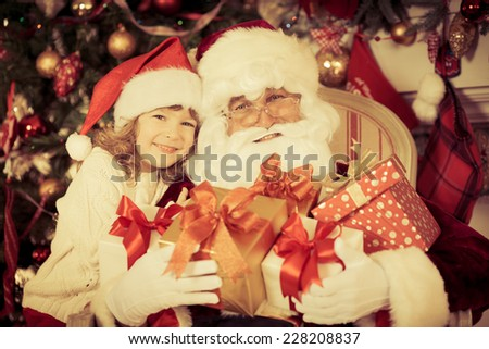 Santa Claus and child against Xmas tree. Kid and grandfather at home. Christmas gift. Family holiday concept - stock photo