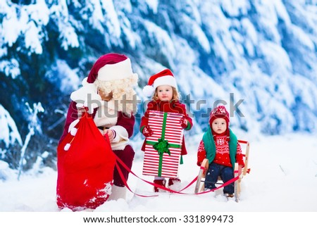 Santa Claus and children opening presents in snowy forest. Kids and father in Santa costume and beard open Christmas gifts. Little girl helping with present sack. Xmas, snow and winter fun for family. - stock photo