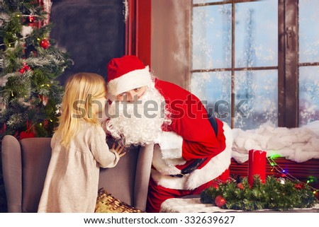 Santa Claus and little girl. Christmas Scene. Girl telling her Christmas wish in Santa Claus near the Christmas Tree - stock photo