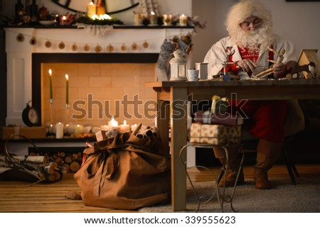 Santa Claus at Home making wooden toys - stock photo
