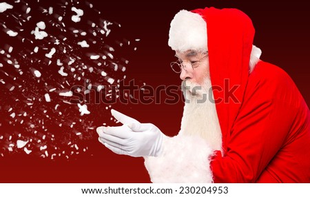 Santa claus blowing away snow from his hands - stock photo