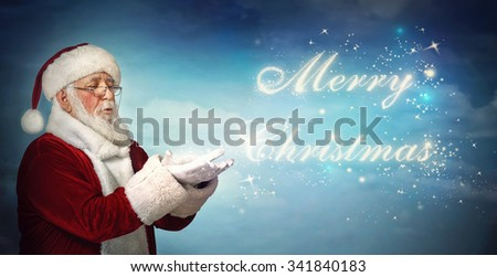 Santa Claus blowing Merry Christmas from snow on blue background - stock photo