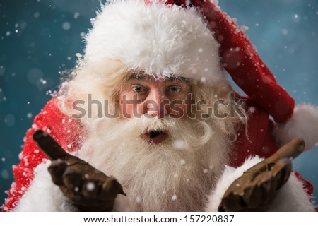 Santa Claus blowing snow and looking at camera outdoors in winter - stock photo