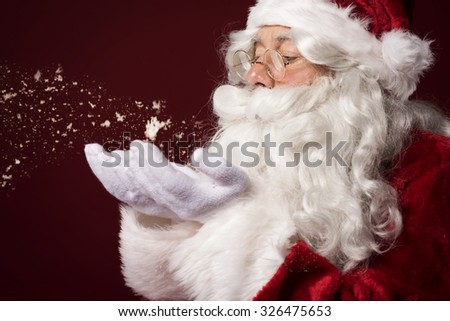 Santa claus blowing some snowflakes - stock photo