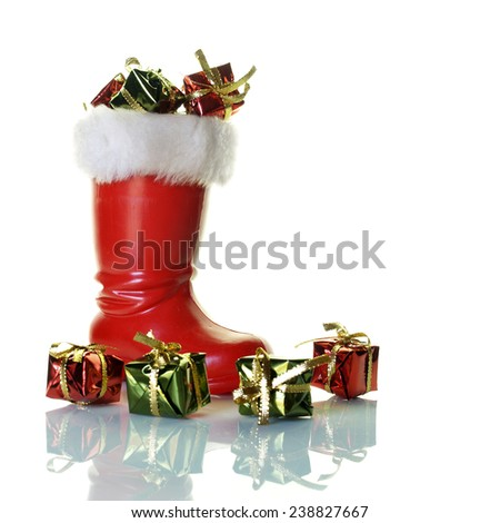 Santa Claus boot full of presents over white         - stock photo