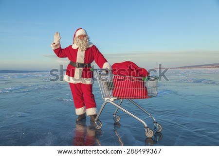Santa Claus carries a shopping cart with gifts in a sack on a winter lake ice - stock photo