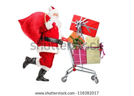 Santa Claus carrying a bag and pushing a shopping cart full of gifts isolated on white background - stock photo