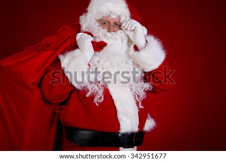 Santa Claus carrying big bag , on red background - stock photo
