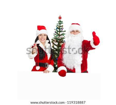 Santa Claus christmas girl hold white board hand show thumb up finger gesture, new year decorated tree with empty copy space for text, isolated on white background - stock photo