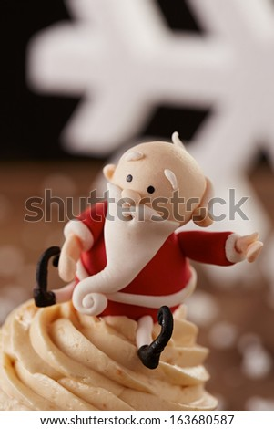 Santa Claus cupcake detail on white snow flakes Christmas background - stock photo