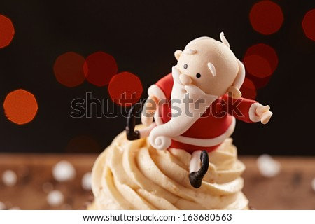 Santa Claus cupcake on white snow flakes Christmas background - stock photo
