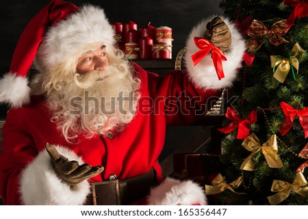 Santa Claus decorating Christmas tree in dark room  - stock photo