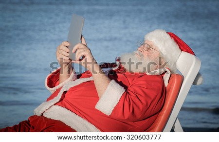 Santa Claus doing a selfie at the beach - stock photo