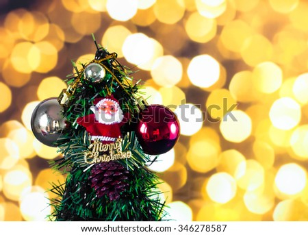 Santa Claus doll against pine nut with ball and Christmas tree on yellow bokeh light background - stock photo