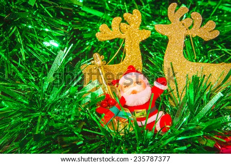 Santa Claus doll and reindeer  with Christmas tree - stock photo