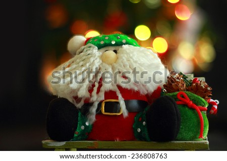 Santa Claus doll with Christmas Trimmings and Christmas Lights on black background - stock photo