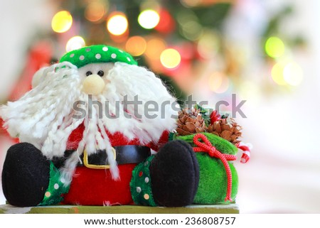 Santa Claus doll with Christmas Trimmings and Christmas Lights on white background - stock photo