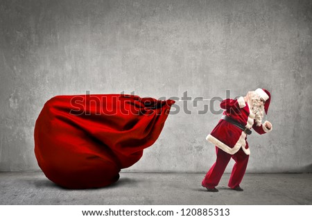 Santa Claus dragging his very large full of presents - stock photo
