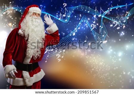 Santa Claus enjoying sound of distant music - stock photo
