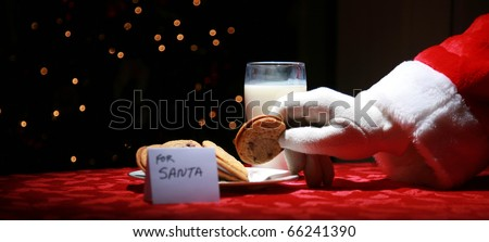 Santa Claus enjoys Cookies and Milk on Christmas Eve - stock photo