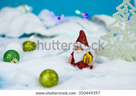 Santa Claus figurine on blue background with christmas ornaments - stock photo