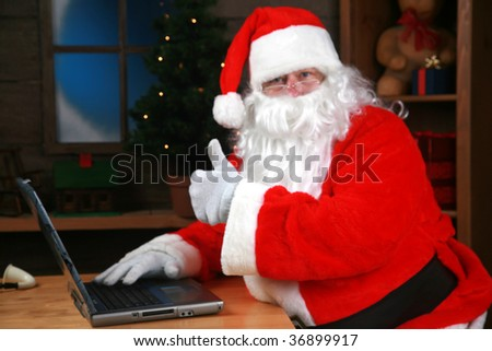 "Santa Claus flashes the ""thumbs up"" sign checking his e mail - stock photo"