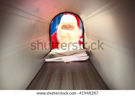 Santa Claus gets his mail from his mail box in the north pole before christmas eve - stock photo