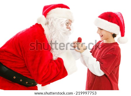 Santa Claus gives a Christmas lollipop to a cute little boy.  Isolated on white.   - stock photo