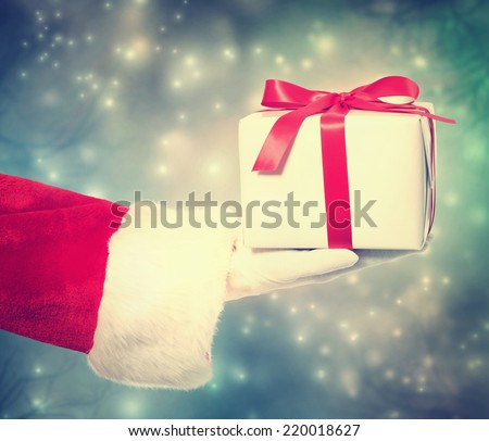 Santa Claus Giving a Christmas Present in Snowing Night - stock photo