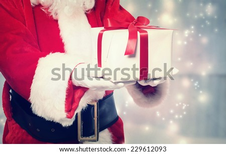 Santa Claus giving a Christmas present with red ribbon - stock photo