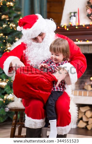 Santa Claus giving a present to kid boy near the fireplace and Christmas tree at home - stock photo
