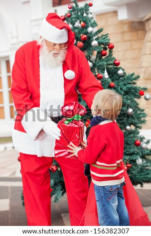 Santa Claus giving gift to boy against Christmas tree - stock photo